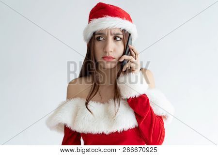 Concerned Christmas Girl Speaking On Phone. Beautiful Young Woman In Santa Hat Speaking On Mobile Ph
