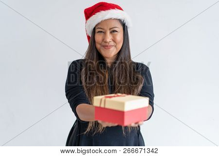 Joyful Christmas Lady Giving Gifts. Positive Mix Raced Woman In Santa Hat Offering Present Box At Ca
