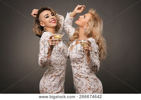 Two Beautiful Young Women With Martini Glasses Isolated