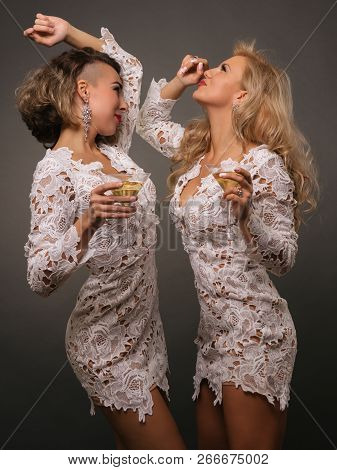 Two Beautiful Young Women With Dancing Martini Glasses Isolated