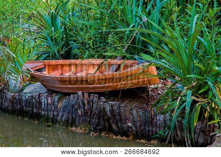 A Small Wooden Canoe Hidden In The Grass, On The River Bank