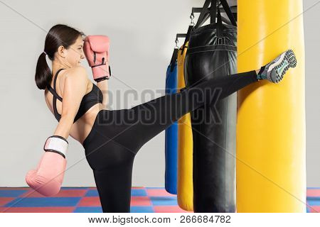 Female Boxer Hitting A Huge Punching Bag At A Boxing Studio. Woman Boxer Training Hard. Thai Boxer P