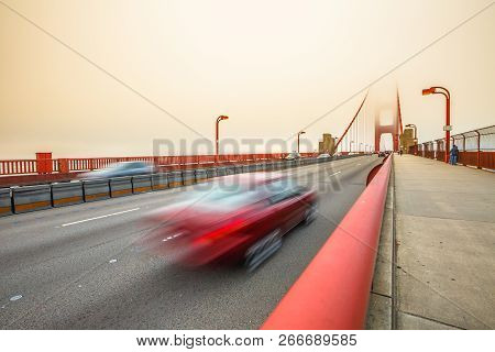 Red Car Crossing Golden Gate Bridge From Presidio Pacific Point To The North. Motion Blur Effect. Sa