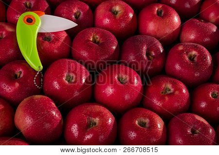 Bright Ceramic Knife On The Background Of Fresh Juicy Apples In Drops Of Water