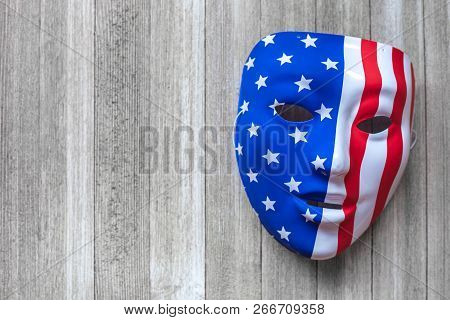 Mask With American Flag Painted Over On A Wooden Background. Conspiracy Theory Concept