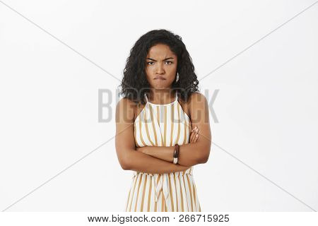 Portrait Of Angry And Mad Cute African American Woman With Curly Hairstyle Crossing Arms On Chest In