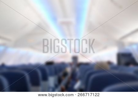 Passenger Sit On Seat In Airplane.  Aisle In Aeroplane Interior. Blur Background