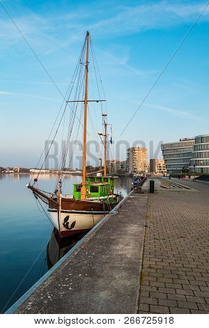 Sailing Ship And Modern Buildings In Rostock, Germany.