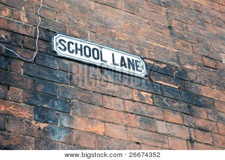 """Road sign on a brick wall reading """"well lane"""""""