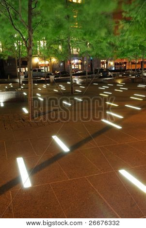 Light floor in Zuccotti Park in lower Manhattan at night in New York, New York.