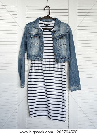 Striped Dress And Denim Jacket On A Hanger. White Wooden Background. Fashionable Wardrobe