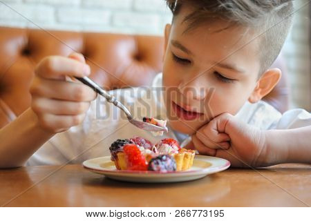 Handsome happy boy in shirt eats cake with berries on table in cafe