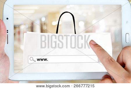 Hand holding tablet with www. on search bar over shopping bag and blur store background on screen, on line shopping ,business, E-commerce, technology and digital marketing background poster