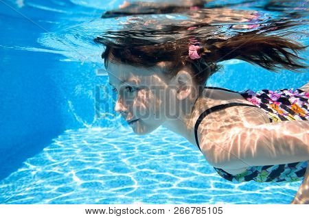 Child Swims In Swimming Pool Underwater, Happy Active Girl Dives And Has Fun Under Water, Kid Fitnes