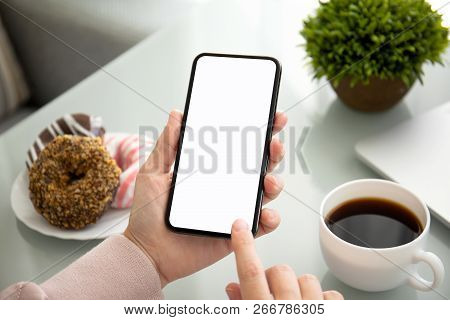 Female Hand Holding Touch Phone With Isolated Screen Above The Table In Cafe