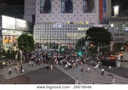 TOKYO - JULY 5: People cross Shibuya Crossing July 5, 2011 in Tokyo, Japan. The crossing is the largest and most famed scramble crosswalk in the world.