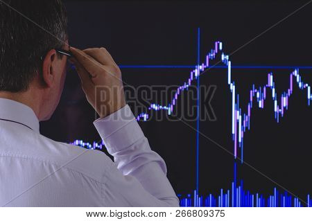 The Investor Is Looking At A Volatile Chart Of Stock Indexes. A Black Day On The Stock Exchange And