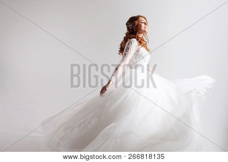 Lovely young woman bride in a lavish wedding dress. Light background. Free space for some design poster