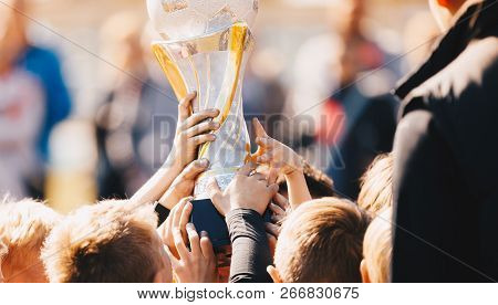 Close-up Of Kids Sports Team With Trophy. Boys Celebrating Sports Achievement. Team Sports Champions