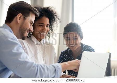 Diverse Happy Interns Listening To Mentor Explaining Online Proj