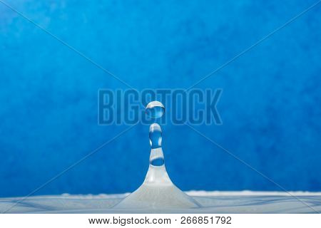 Water Droplet Falling Into Water With Blue Background.