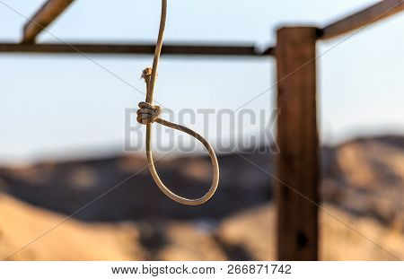Rope Noose Hanging Outdoors In Sandy Wilderness On Sunny Blue Sky Background. Scaffold For Committin