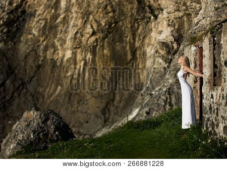 Beautiful Blonde Woman In White Long Dress Outdoor, Enjoys The Sunlight Next To The Door Of A Ruined