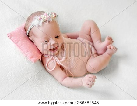 Little smiling baby in pink knitted suit joyfully lying on pink dotted pillow and white soft blanket