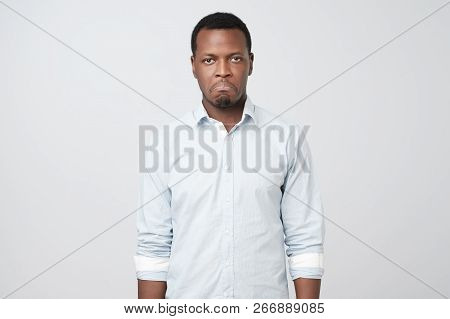 Young African Man Looks Sad And Offended, Frowned Eyebrows, Lips Pout, Wears White Shirt