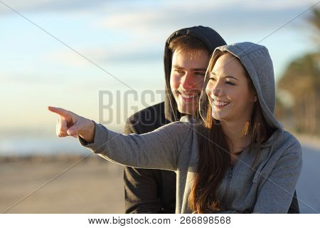 Couple Of Happy Teens Pointing At Horizon On Tghe Beach At Sunrise