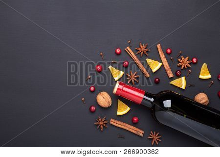 Bottle Of Red Wine And Spice For Mulled Wine On Black Background. Cinnamon, Anise Stars, Orange, Bro