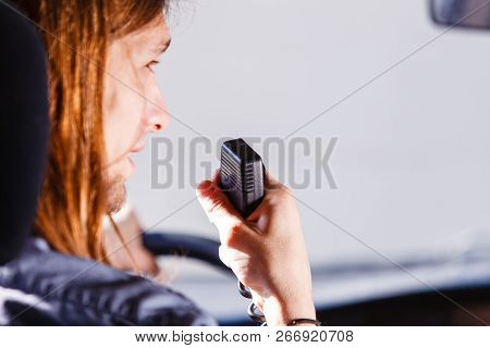 Talking while drive, auto walkie talkie, comunication concept. Young man driving car using cb radio poster