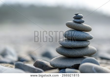 Balance And Wellness Concept. Close-up Of Ocean Stones Balanced On Rocks And Ocean Driftwood. Low De