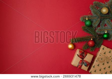 Christmas Holidays Composition On Red Background With Copy Space For Your Text. Xmas Tree Fir Branch