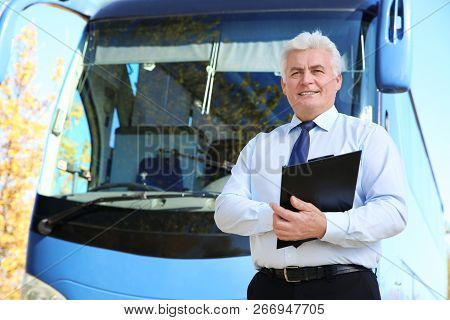 Professional Driver With Clipboard Near Bus. Passenger Transportation