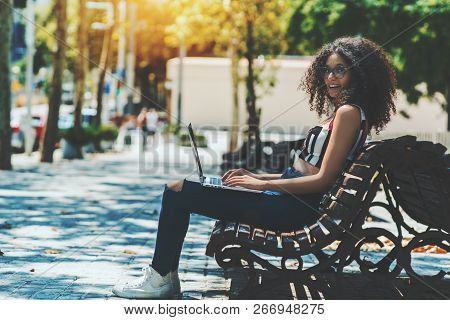 A Laughing Cute Hipster Girl Is Sitting On A Park Bench And Working On Her Laptop; Young Caucasian W