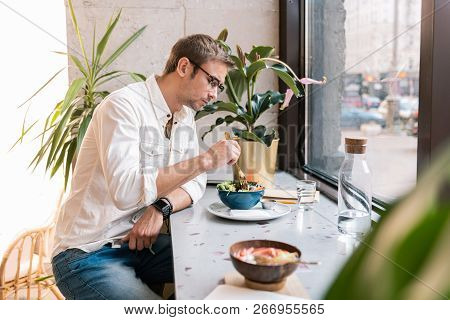 Stylish Handsome Man Wearing White Shirt Eating Lunch In Vegan Cafe