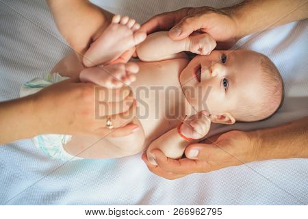 Because Care Begins In Family. Newborn Baby Given Massage By Parents. Newborn Baby Care. Happy Paren