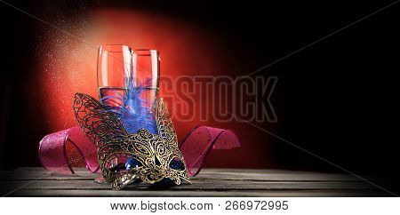 Two Glasses Of Champagne With Mask On The Table. Event Or Party Celebration