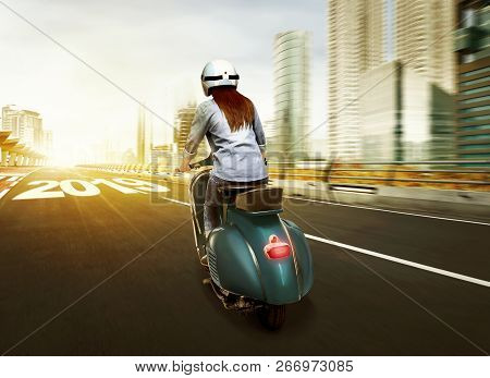 Young Asian Woman In Helmet Riding A Scooter On The City With 2019 Number In Asphalt Road. Happy New