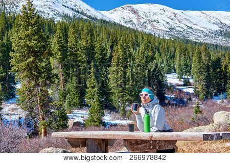 Woman hiker having rest on a trail in Rocky Mountains, Colorado, USA.