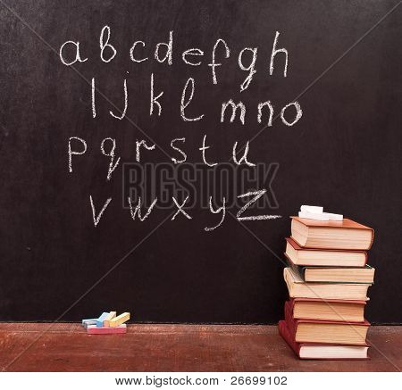 Alphabet on a chalkboard with books
