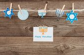 flat lay with happy hannukah card and holiday paper signs pegged on rope on wooden tabletop, hannukah concept poster