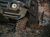 4x4 or 4WD car with wheels in mud in the forest, off road. Car stuck in puddle of mud. Wheel covered with dirt. Extreme entertainment concept. poster