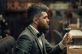 Date meeting of hipster awaiting in pub. Perfect wine. bar customer sit in cafe drinking alcohol. Businessman with long beard drink in cigar club. Bearded man rest in restaurant with wine glass. poster