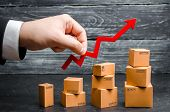 A businessman's hand holds a red arrow up above cardboard boxes folded incrementally. Sales growth and increase in exports of goods and services. Growth profits and the number of buyers. poster