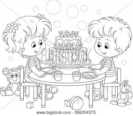 Happy Little Kids Friendly Smiling And Sitting Round Their Festive Board With A Fancy Birthday Cake