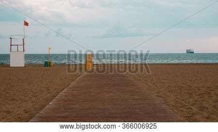 Abandoned Beach With Wooden Planks Due To The Storm. With A Red Flag Warning Of Danger. In The Backg
