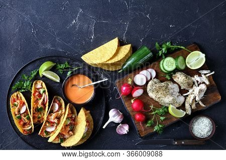 Buffalo Chicken Corn Taco Shells Loaded With Fresh Greens And Vegetables On A Black Plate With Lime