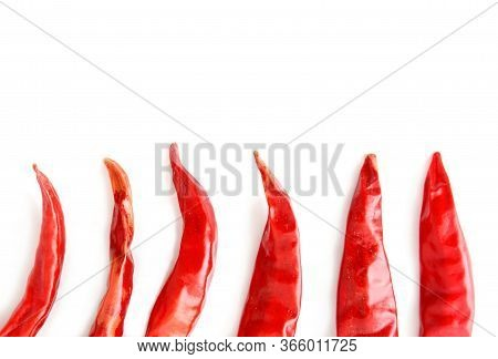 Top View Of Dried Red Hot Chilli Peppers Halves Arranged In A Row. It Looks Like A Chilli Flames On